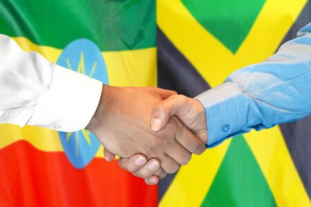 Business handshake on the background of two flags. Men handshake on the background of the Ethiopia and Jamaica flag. Support concept Zdjęcie Seryjne
