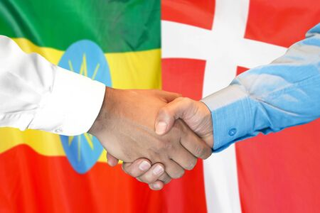 Business handshake on the background of two flags. Men handshake on the background of the Ethiopia and Denmark flag. Support concept Zdjęcie Seryjne