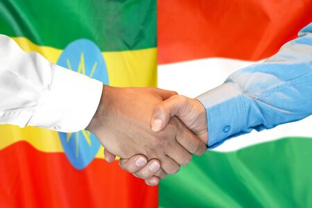 Business handshake on the background of two flags. Men handshake on the background of the Ethiopia and Hungary flag. Support concept Zdjęcie Seryjne