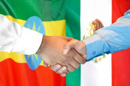Business handshake on the background of two flags. Men handshake on the background of the Ethiopia and Mexico flag. Support concept