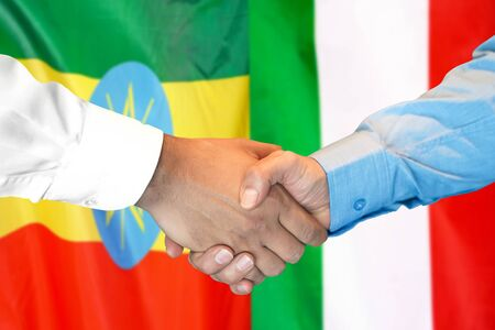 Business handshake on the background of two flags. Men handshake on the background of the Ethiopia and Italy flag. Support concept