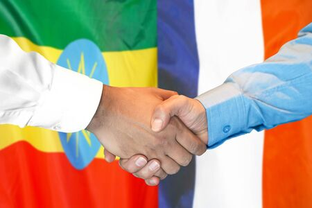 Business handshake on the background of two flags. Men handshake on the background of the Ethiopia and France flag. Support concept