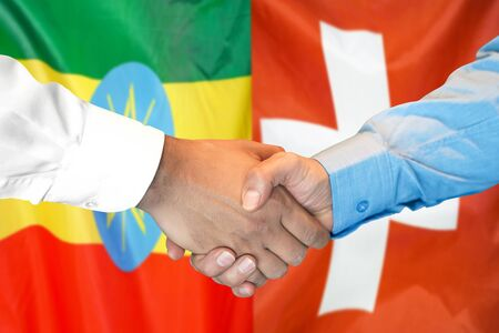 Business handshake on the background of two flags. Men handshake on the background of the Ethiopia and Switzerland flag. Support concept