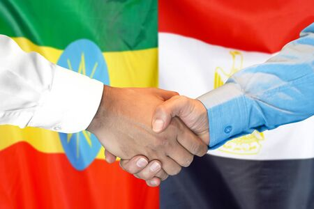 Business handshake on the background of two flags. Men handshake on the background of the Ethiopia and Egypt flag. Support concept