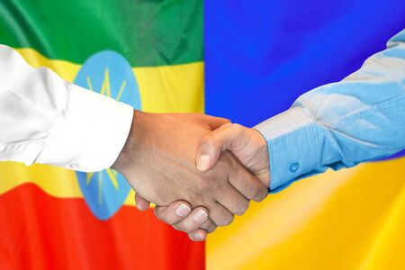 Business handshake on the background of two flags. Men handshake on the background of the Ethiopia and Ukraine flag. Support concept Zdjęcie Seryjne