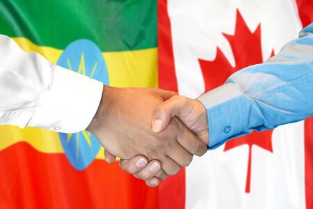 Business handshake on the background of two flags. Men handshake on the background of the Ethiopia and Canada flag. Support concept