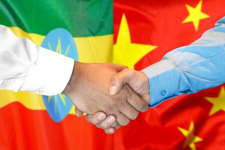 Business handshake on the background of two flags. Men handshake on the background of the Ethiopia and China flag. Support concept
