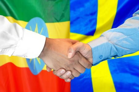 Business handshake on the background of two flags. Men handshake on the background of the Ethiopia and Sweden flag. Support concept