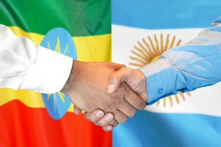 Business handshake on the background of two flags. Men handshake on the background of the Ethiopia and Argentina flag. Support concept
