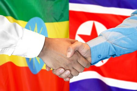 Business handshake on the background of two flags. Men handshake on the background of the Ethiopia and North Korea flag. Support concept