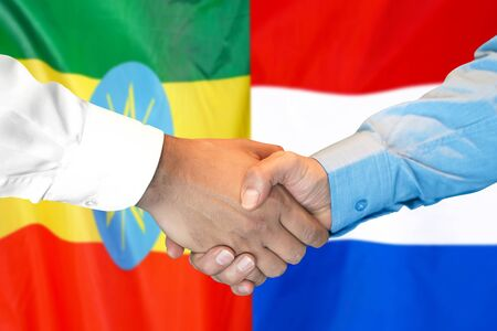 Business handshake on the background of two flags. Men handshake on the background of the Ethiopia and Dutch flag. Support concept
