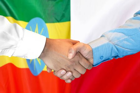 Business handshake on the background of two flags. Men handshake on the background of the Ethiopia and Poland flag. Support concept Zdjęcie Seryjne