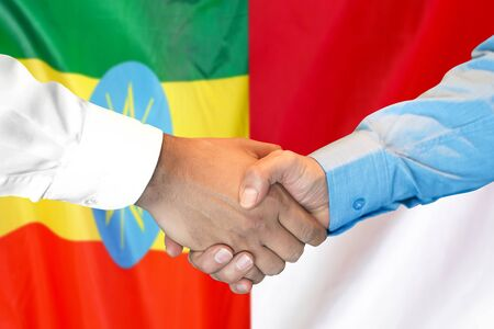 Business handshake on the background of two flags. Men handshake on the background of the Ethiopia and Monaco flag. Support concept