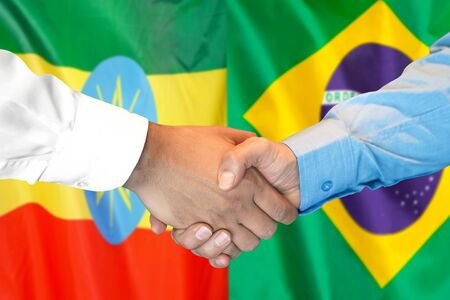 Business handshake on the background of two flags. Men handshake on the background of the Ethiopia and Brazil flag. Support concept Zdjęcie Seryjne