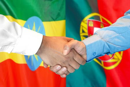 Business handshake on the background of two flags. Men handshake on the background of the Ethiopia and Portugal flag. Support concept