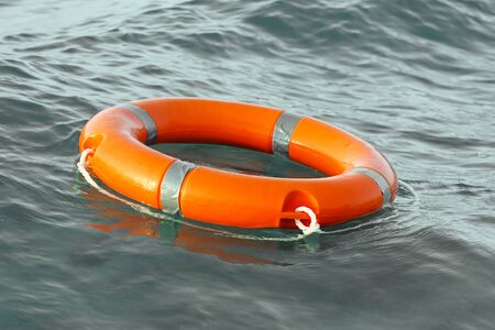 Orange lifebuoy in stormy sea. Life ring floating on top of water. Life ring in stormy ocean.