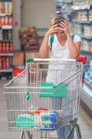 Upset woman in a supermarket with an empty shopping trolley. Crises, rising prices for goods and products. Woman shopping at the supermarket. Imagens