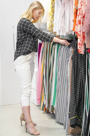 Girl, choose new things in the store. Beautiful young female shopper chooses liked things in the boutique. A young girl chooses things on a hanger in a store.