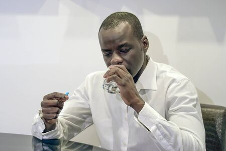 Sick elderly african man holding pill glass of water at home. Depressed unhealthy man, about to take antidepressant pill, emergency contraceptive, painkiller for painful periods.