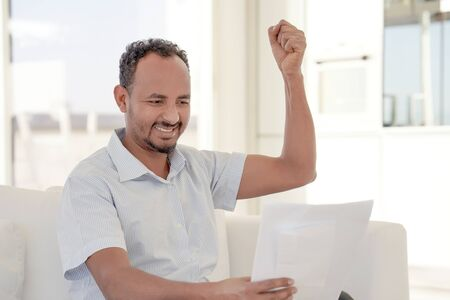 African male reads a letter with good news sitting on the sofa at home. An euphoric male is happy after reading good news in a written letter, approving a loan.