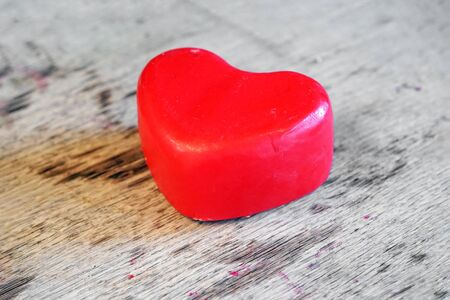 A head of red Dutch cheese in the shape of a heart lies on a wooden board in a private dairy store. St. Valentine's Day.