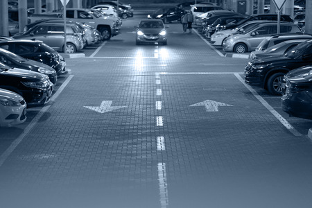 Parking cars with people. Many cars in parking garage interior, industrial building. Underground parking with cars. Toning