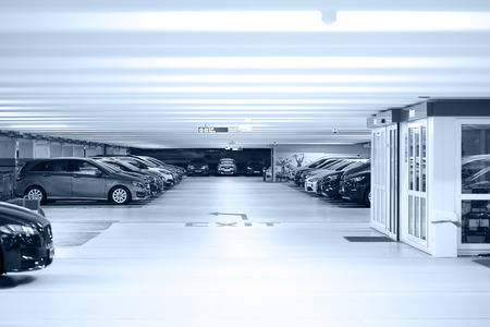Parking cars without people. Many cars in parking garage interior, industrial building. Underground parking with cars.Toning