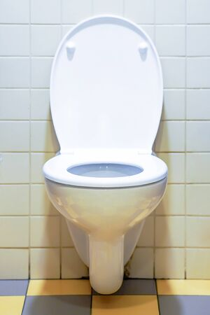 Close-up of toilet bowl. White toilet in the bathroom. Public toilet in the airport or restaurant, cafe.