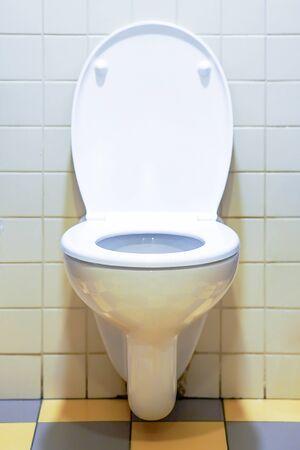 Nahaufnahme der Toilettenschüssel. Weiße Toilette im Badezimmer. Öffentliche Toilette im Flughafen oder Restaurant, Café.