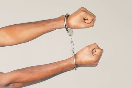 Close-up hands arrested african man. African hands in handcuffed isolated on gray background. Prisoner or arrested terrorist hands in handcuffs Stock Photo