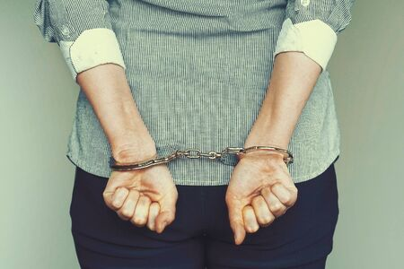 Arrested woman handcuffed hands at the back. Prisoner or arrested terrorist, hacker, bribetaker, close-up of hands in handcuff.