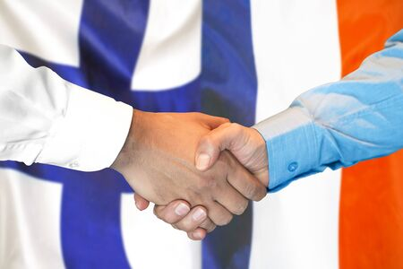Business handshake on the background of two flags. Men handshake on the background of the Finland and France flag. Support concept Stock fotó