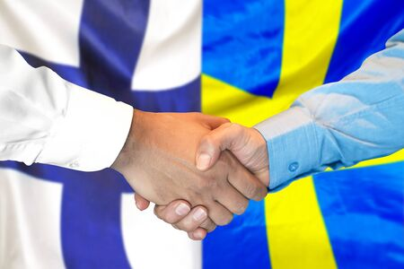 Business handshake on the background of two flags. Men handshake on the background of the Finland and Sweden flag. Support concept