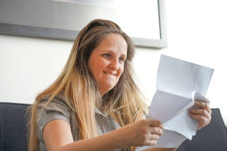 Portrait of woman enjoying good news in writing. The girl reads a letter with good news sitting on the sofa at home. An euphoric girl is happy after reading good news in a written letter, approving a loan.