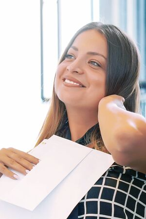 Portrait of woman enjoying good news in writing. The girl reads a letter with good news. An euphoric girl is happy after reading good news in a written letter, approving a loan.