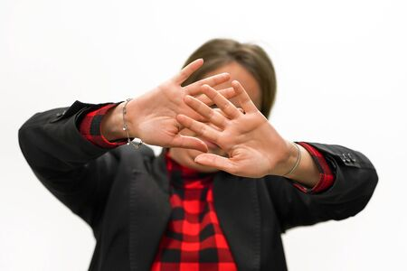 Woman holding her hand stretched out toward the camera, covering her face, avoiding to be seen or stopping a problems. Woman hide her face at hand isolated on white background.