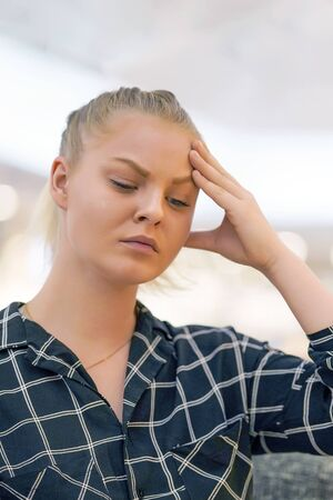 Portrait of young woman suffering from headache migraine pain. Health problem, stress and depression. Female holds head with hand. Concept of health.