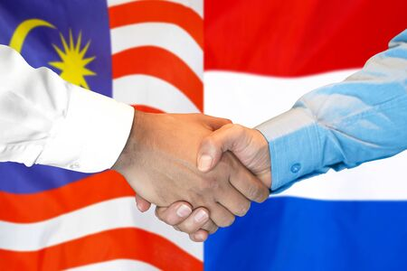 Business handshake on the background of two flags. Men handshake on the background of the Malaysia and Netherlands flag. Support concept Stock fotó