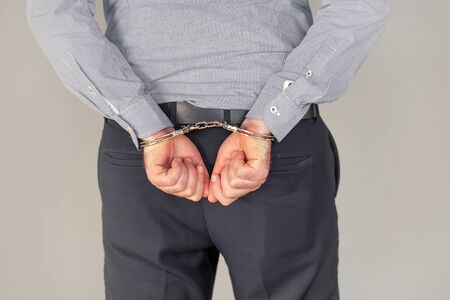 Arrested man handcuffed hands at the back. Isolated on gray background. Businessman in office in handcuffs holding a bribe. Arrested man in handcuffs. Criminal hands locked in handcuffs.