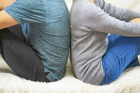 Couple with their backs turned to each other sitting on white couch. ?ngry and upset couple turning their back on each other in bed.