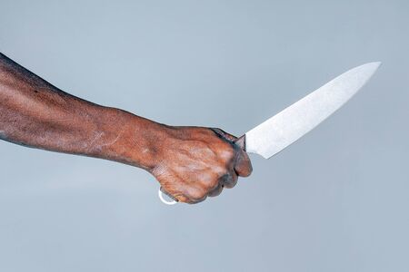 African man hold knife - aggression. Big kitchen knife in man hand. Large kitchen knife in a man's hand. Hand of african man holding a knife isolated on a blue background. Stock Photo
