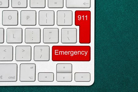 White computer keyboard and red buttons with word emergency and number 911. Dark background. Close-up.