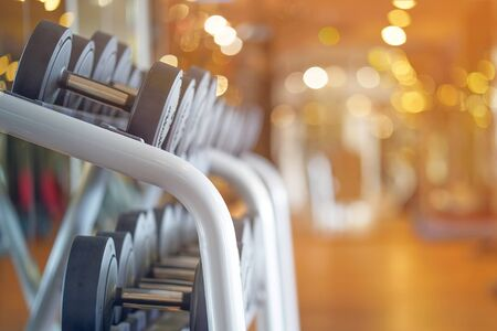 Rows of dumbbells in the gym. Toning.