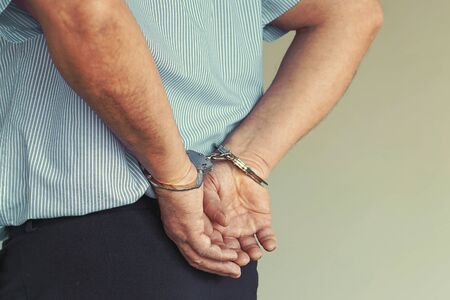 Arrested man handcuffed hands at the back. Prisoner or arrested terrorist, close-up of hands in handcuffs.