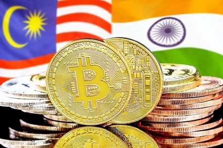 Concept for investors in cryptocurrency and Blockchain technology in the Malaysia and India. Bitcoins on the background of the flag Malaysia and India.