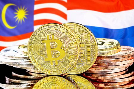 Concept for investors in cryptocurrency and Blockchain technology in the Malaysia and Netherlands. Bitcoins on the background of the flag Malaysia and Netherlands.