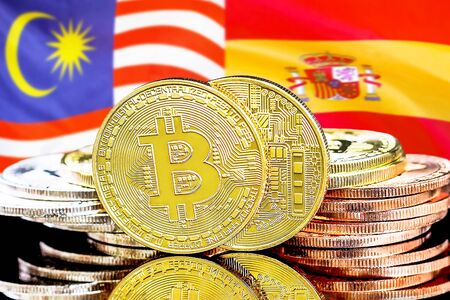Concept for investors in cryptocurrency and Blockchain technology in the Malaysia and Spain. Bitcoins on the background of the flag Malaysia and Spain.