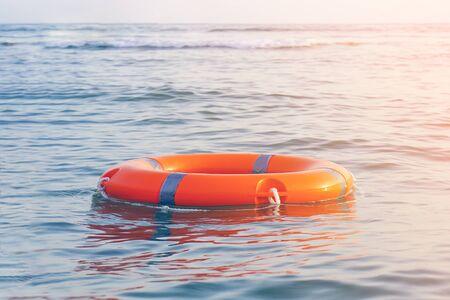 Orange lifebuoy in sea on water. Life ring floating on top of water. Life ring in ocean.