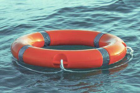 Orange lifebuoy in sea on water. Life ring floating on top of water. Life ring in ocean.