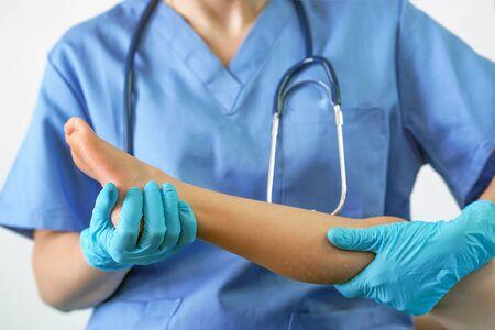 Hand des Arztes, der das Bein des Patienten hält, Untersuchung von Patienten im Krankenhaus. Chirurg, chirurgischer Arzt, Anästhesist, der Beinpatienten hält. Professionelle ER-Chirurgie, Gesundheitskonzept.